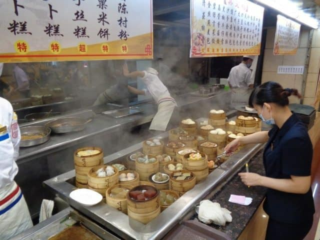 The hotel staff prepare an array of breakfast dishes, including jiaozi, sweet pork buns and chicken feet.