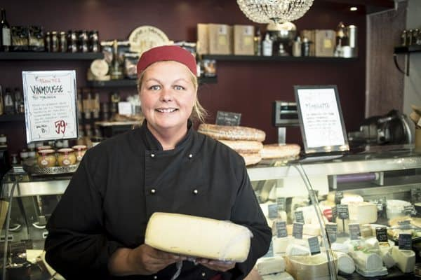 Vera stands with local cheese at her downtown store.