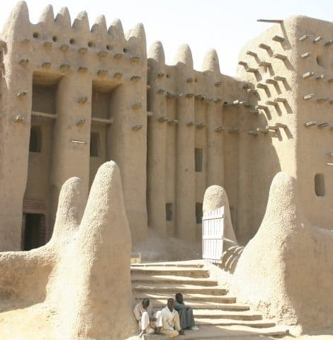 In Djenne, Mali everything is made of mud. Photographed are three boys sitting in front of the impressive mud architecture. James Dorsey Photos.