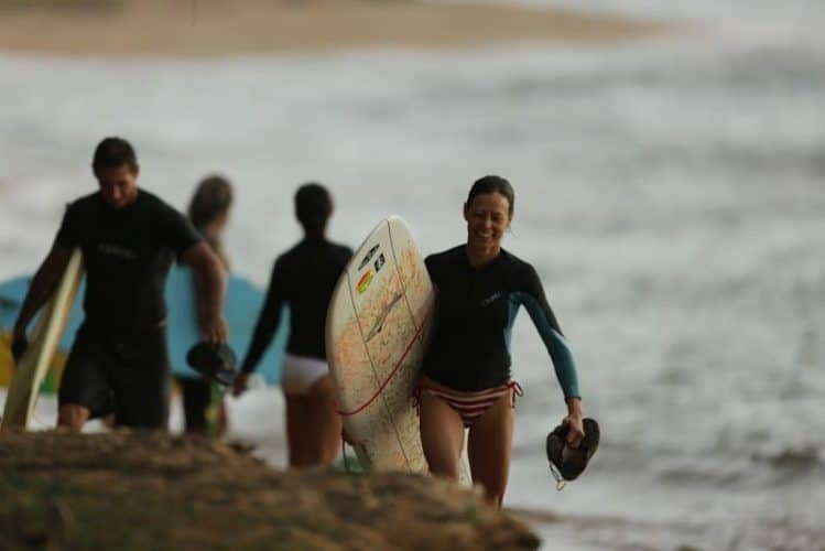 Noelle Salmi in the late afternoon after an epic surf session at Pakalas Kauai HI with Clay Wolcott Cailtin Pardo de Zela and Sarah Barton in background. Photo by Ry Cowan