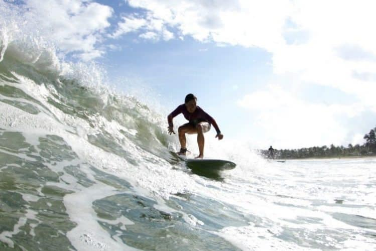 Noelle Salmi rides a wave in Hanalei Bay Kauia HI. Photograph by Ry Cowan