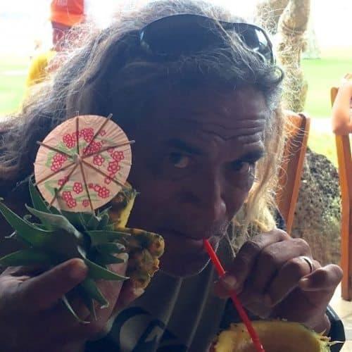 Titus Kinimaka takes a sip of pina colada at Dukes Restaurant Lihue Kauai HI. Photo by Noelle Salmi