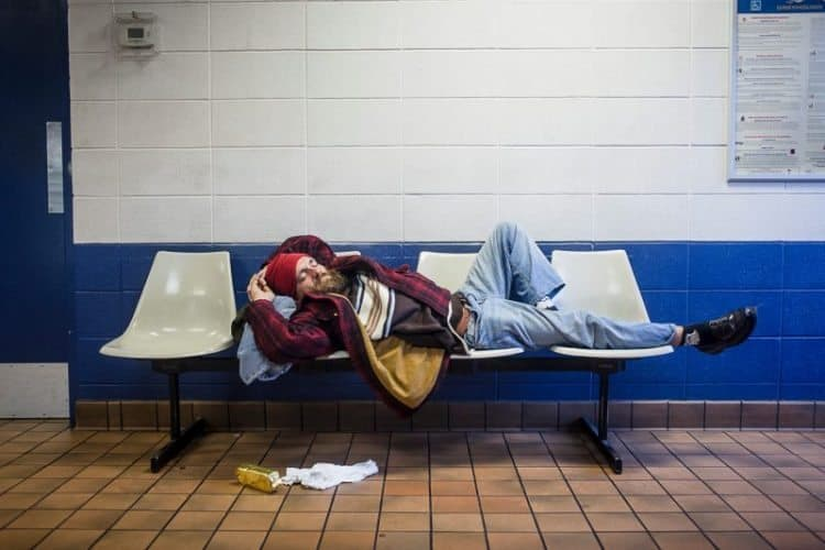 A man sleeps on a bench in a bus station, somewhere in the United States.