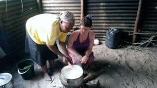 Volunteers help prepare a traditional Zulu meal