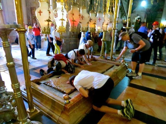 People praying in The Church of the Holy Sepulcher.