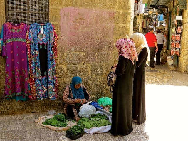 A woman in the Muslim Quarter making grape leaves to sell.