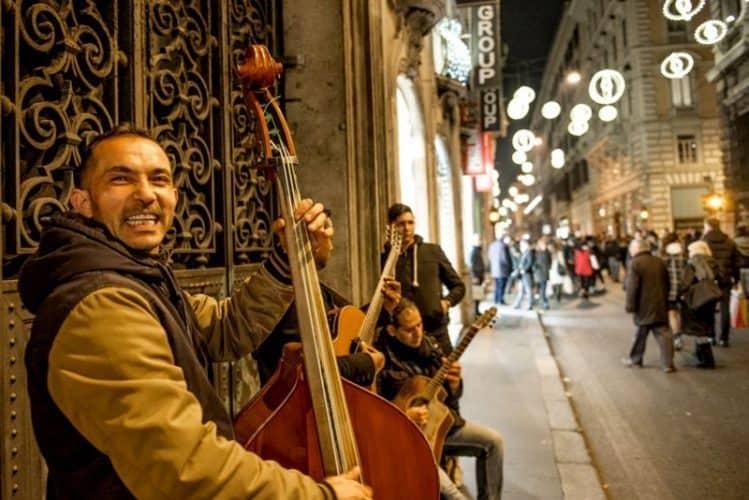 A Bulgarian string trio play Christmas carols on Via del Corso. Photo by Marina Pascucci