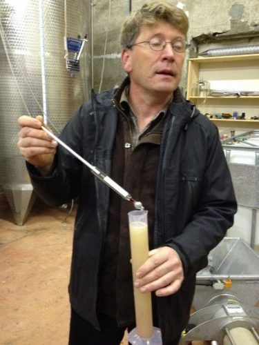 Sylvain shows us how the fermentation progress is checked during aging.