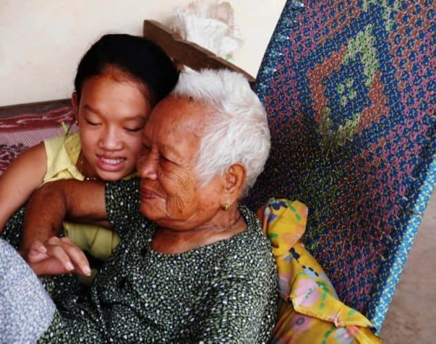 Two generations of Cambodian women sit comfortably, enjoying each other's company.