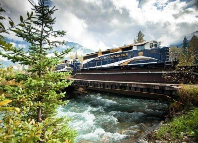 The train crosses over a stream in the Canadian Rockies.