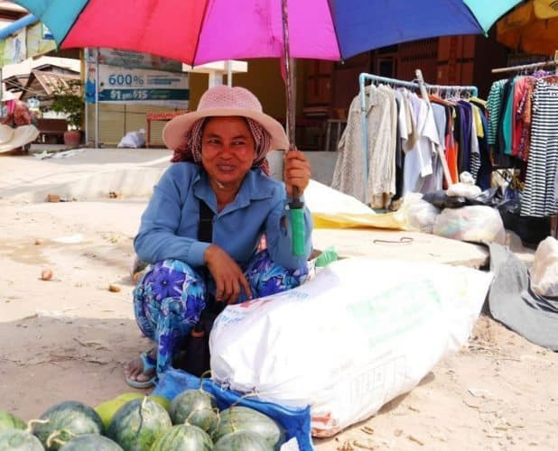 A street vendor shading herself from the harsh Cambodian sun while selling fresh produce and clothes