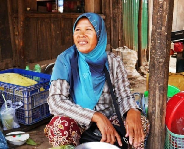 A woman selling fish and poultry at the village market.