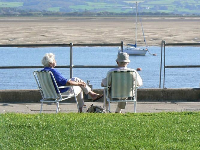 A couple enjoys the sun on the coast of Wales. Max Hartshorne photo.