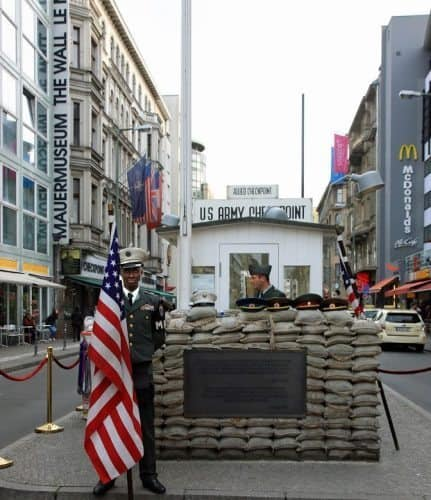 "A McDonalds, The Wall Museum, and a large number of tourists pass by what the world calls ""Checkpoint Charlie,"" which was the border between East and West Berlin"