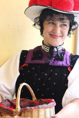 Wearing a Bollenhut hat adorned with cherry-red pom-poms, Nicole Djandji, a delightful Freiberg city tour guide looks, fetching in her traditional Black Forest costume once worn by unmarried girls.