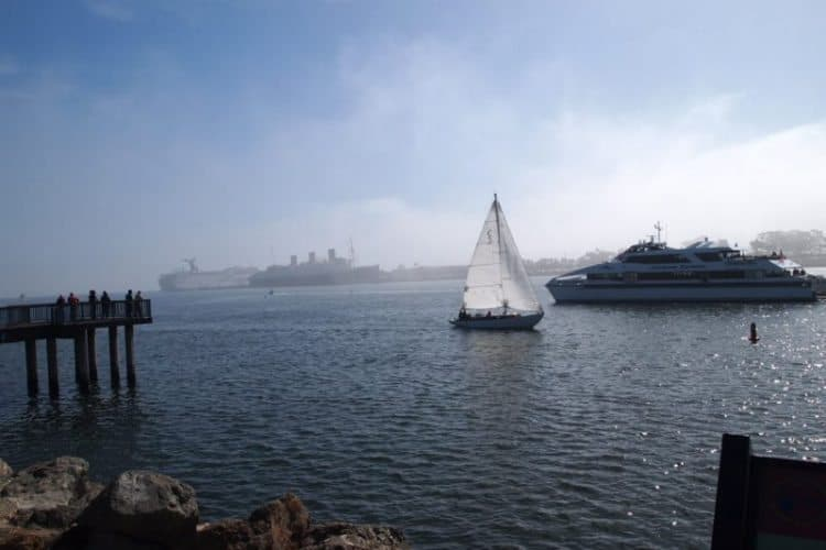 Catalina ferry with Queen Mary behind in Long Beach Rainbow Harbor.