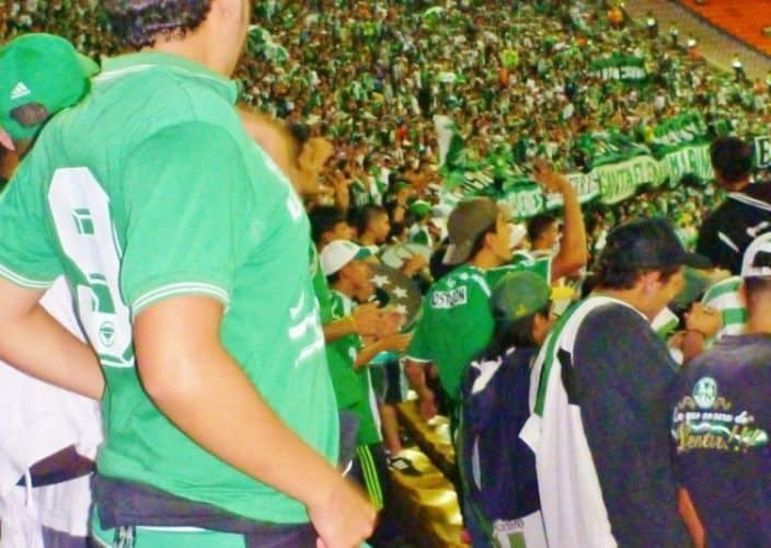 Estadio Atanasio Girardot, full of green and white striped Nacional fans.