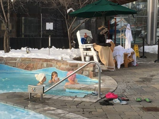 A lifeguard is bundled up while guests enjoy the heated pool at the Ritz Carlton Tremblant.