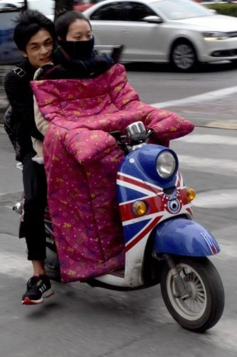 A scooter driver dressed for winter on a Beijing street.