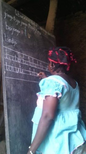 Leading the lesson at the blackboard.