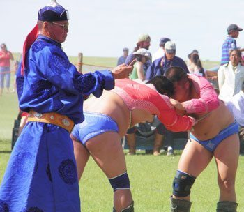 A referee texting during the wrestling competition at the Naadam Festival's Three Games of Men