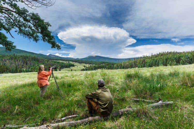 A photographer shooting in a meadow as cumulonimbus capillatus clouds form over Vermejo Park Ranch, New Mexico. James Reidy photos