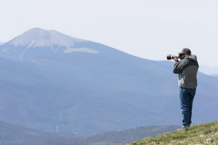 Photographer on ridge above timberline looking into valleys below at East Fork overlook, Vermejo Park Ranch, Colorado, USA. Overlook is in Colorado, but most of Vermejo is in New Mexico