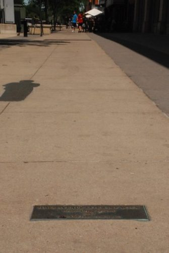 The Iowa City Literature Walk is marked by this brass plaque in the sidewalk.