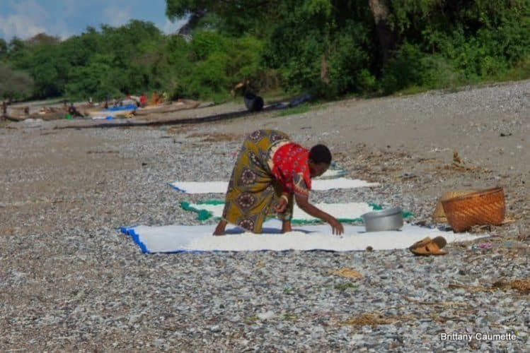 A woman spreads her cassava out to dry in the sun along the edge of Lake Malawi.