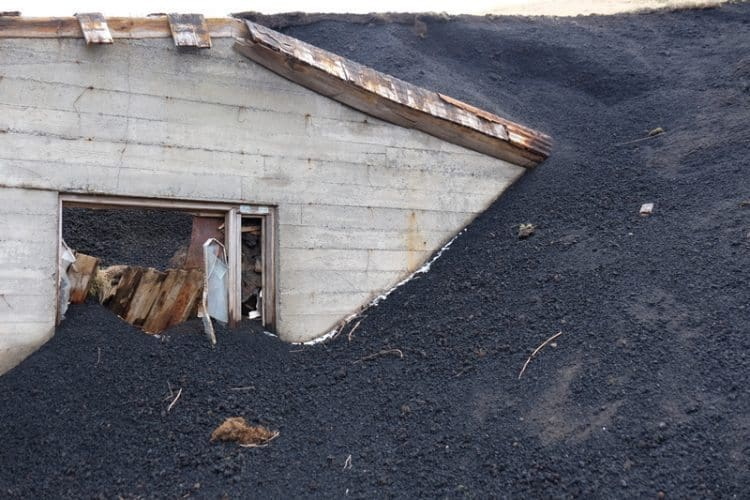 The remains of a house buried by the Eldfell eruption, lava on a house.