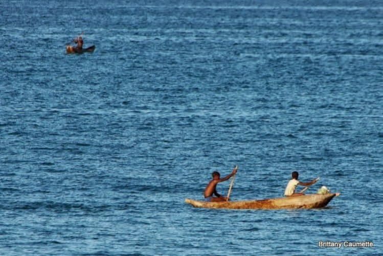 Local boys paddling out to better fishing territory on their hand-carved wooden pirogue.