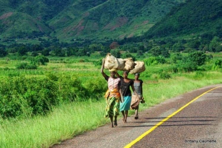 Women walking their goods along the main highway to market.