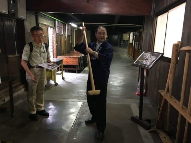 At the Kiminoi sake distillery, the sake brewer shows us how they use a paddle to make sake.
