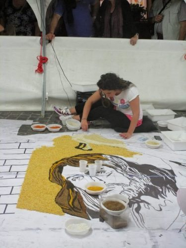 Artists work feverishly the night before the event to create the complex art to be transformed by flower petals.
