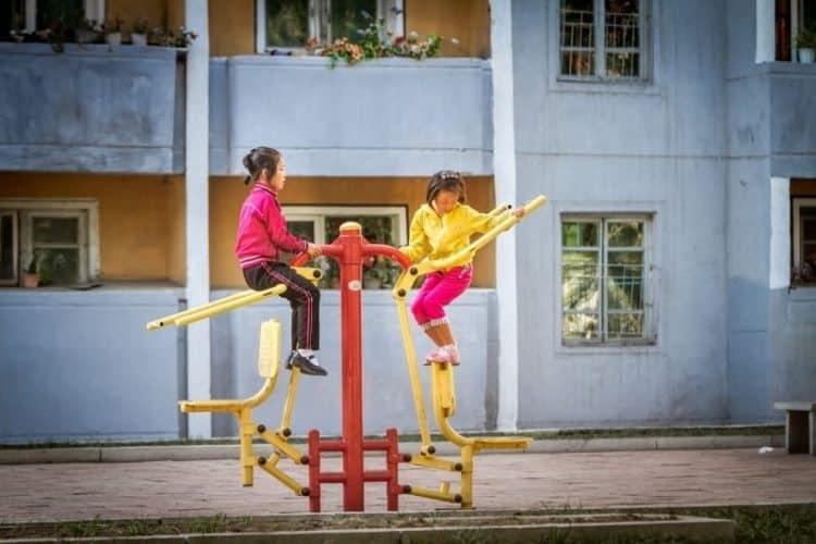 School children play on new sports equipment at their school.