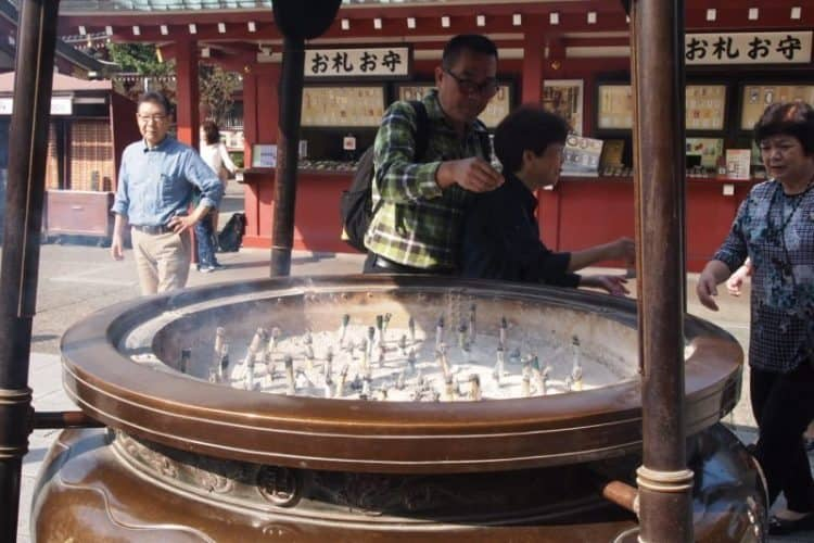 Giving alms for the dead at the Asakusa Temple in Tokyo.