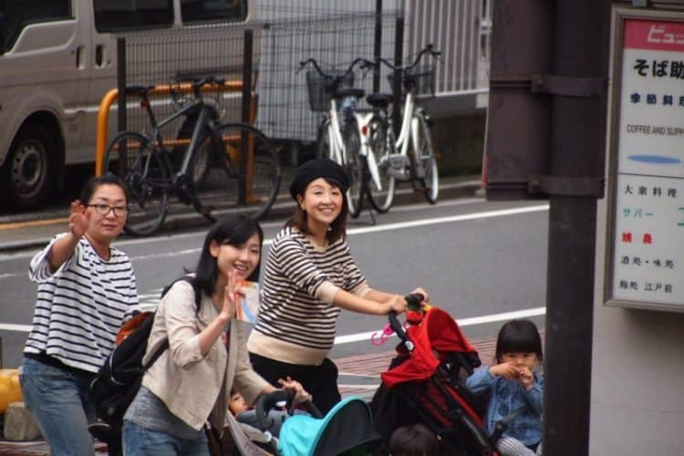 Waving to the Tokyo Sky Bus, an open-top tour bus that shows tourists the city in a circular route around Tokyo.