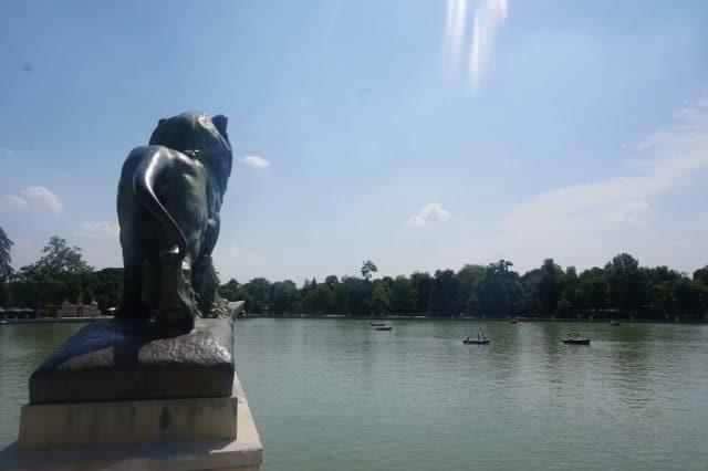 Lion statue overlooking Retiro Pond in Buen Retiro Park