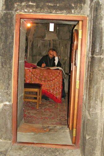 Perturbed priest inside Geghard Monastery vestry in Armenia