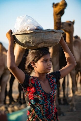 A young girl carrying food for the many vendors and locals who attend the fair.