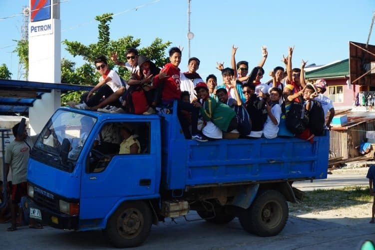 Locals in St Monica, a popular way to get around the island, in the back of a dump truck.