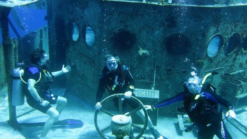 Divers can easily access the ship's wheel and other aspects of the USS Kittiwake, a submarine fighting ship that was sunk in the Grand Caymans as a permanent reef. Tab Hauser photo.