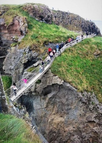 A daring group of tourists brave the Carrick-a-Rede Rope Bridge on this windy