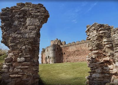 Viewed through its foreworks, Tantallon Castle's massive curtain wall looms high.
