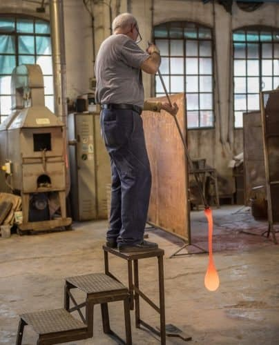 Glassblowing requires both strength and stamina, especially with larger pieces, as seen here with this artisan.