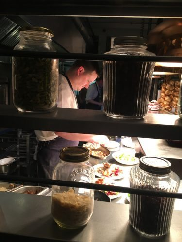 A chef prepares a small plate at Evelyn's Cafe, a cozy restaurant in the Northern Quarter, filled with music clubs and nightclubs.