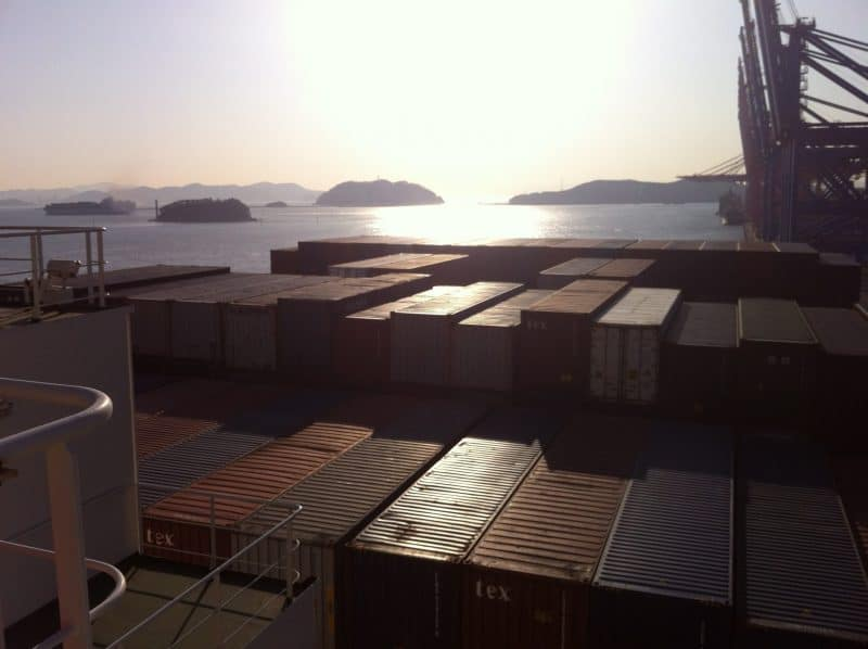 Containers line the decks of a container ship that takes passengers, docked in South Korea.
