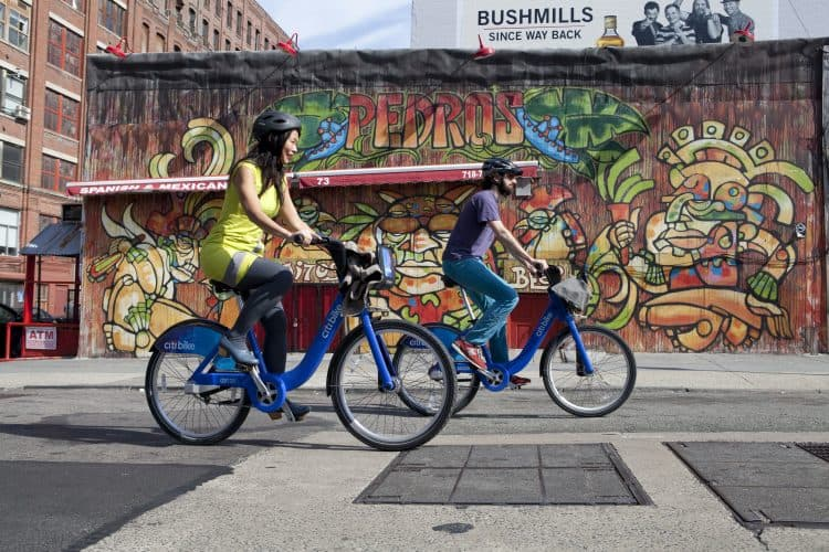 Two bicyclists cruising through downtown Brooklyn on a Citi Bike. Photo by Lars Klove/NYC Bike