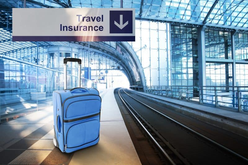 Travel Insurance. Blue suitcase at the railway station