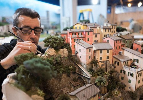 An artist working on creating the miniature houses in the Gulliver's Gate exhibit. Photo by reservenewyorkcity.com